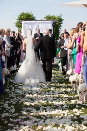 Bride escorted down aisle by her father on grass