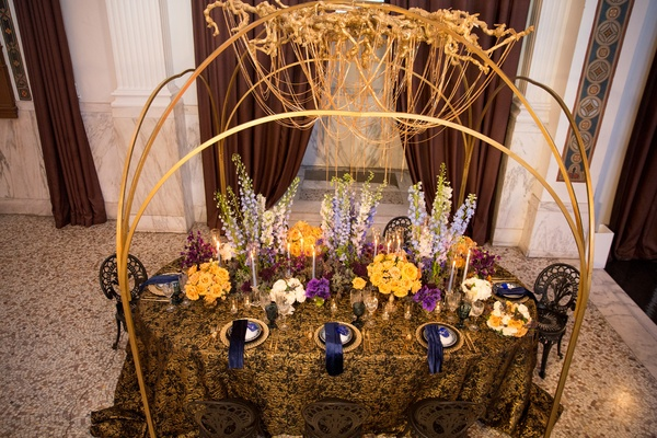 wedding styled shoot, golden chain chandelier, gold and black linen, colorful florals