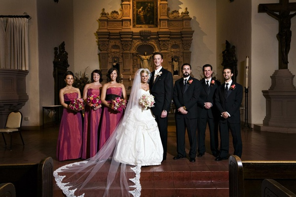 Bride and groom at church altar with bridesmaids and groomsmen