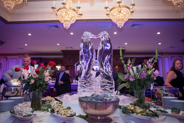 ashley alexiss reception cocktail hour food ice bar with ice sculpture of penguins purple lighting