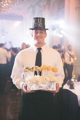 New Year's Eve wedding waiter with black New Year's Eve party hat holding deep fried oreos macarons