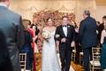 Bride in Legends Romona Keveza off shoulder wedding dress with groom arm in arm flower wall