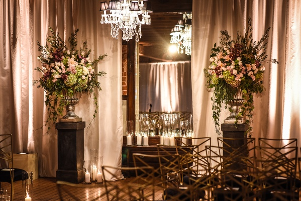 blush, burgundy, green floral arrangement on stand with crystal chandelier at ceremony