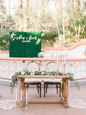 wedding reception outdoor courtyard wood sweetheart table greenery gold candlesticks spanish tile