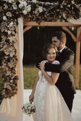 fall wedding styled shoot outdoor ceremony wood arbor gold leaf white orchid drapery bride overskirt