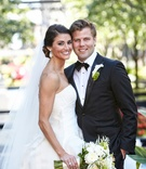 a loving couple smiling for the camera in a white wedding dress and black tuxedo with white flowers