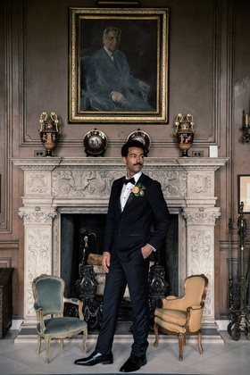 styled wedding shoot groom in tuxedo in front of elegant fireplace with portrait