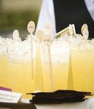 Yellow wedding drinks with custom swizzle sticks