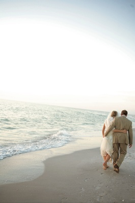 Bride and groom walking barefoot on beach at sunset