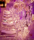 Violet lighting illuminating crystal glassware and table