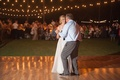 Bride in a Love Marley dress with illusion neckline, tulle skirt dances with father in grey pants