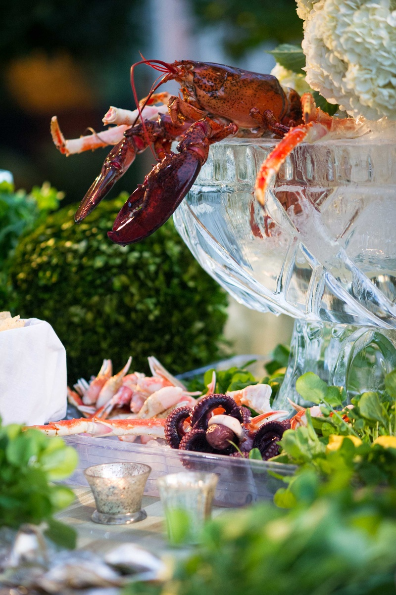 Lobster, crab, seafood in ice sculpture bowls and vases at wedding cocktail hour