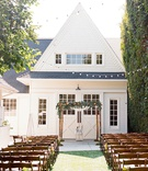 Wedding ceremony outside string lights wood branch chuppah greenery renovated victorian farmhouse