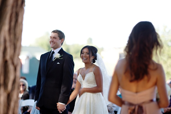Bride in a wedding dress with spaghetti straps holds hands with groom in black suit and tie