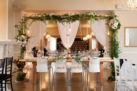 a unique tablescape with an urban chic concept for a head table with arch and foliage hanging items