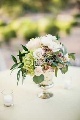 Silver mercury glass vessel with green leaves, green hydrangea, pink hydrangea, white spray rose