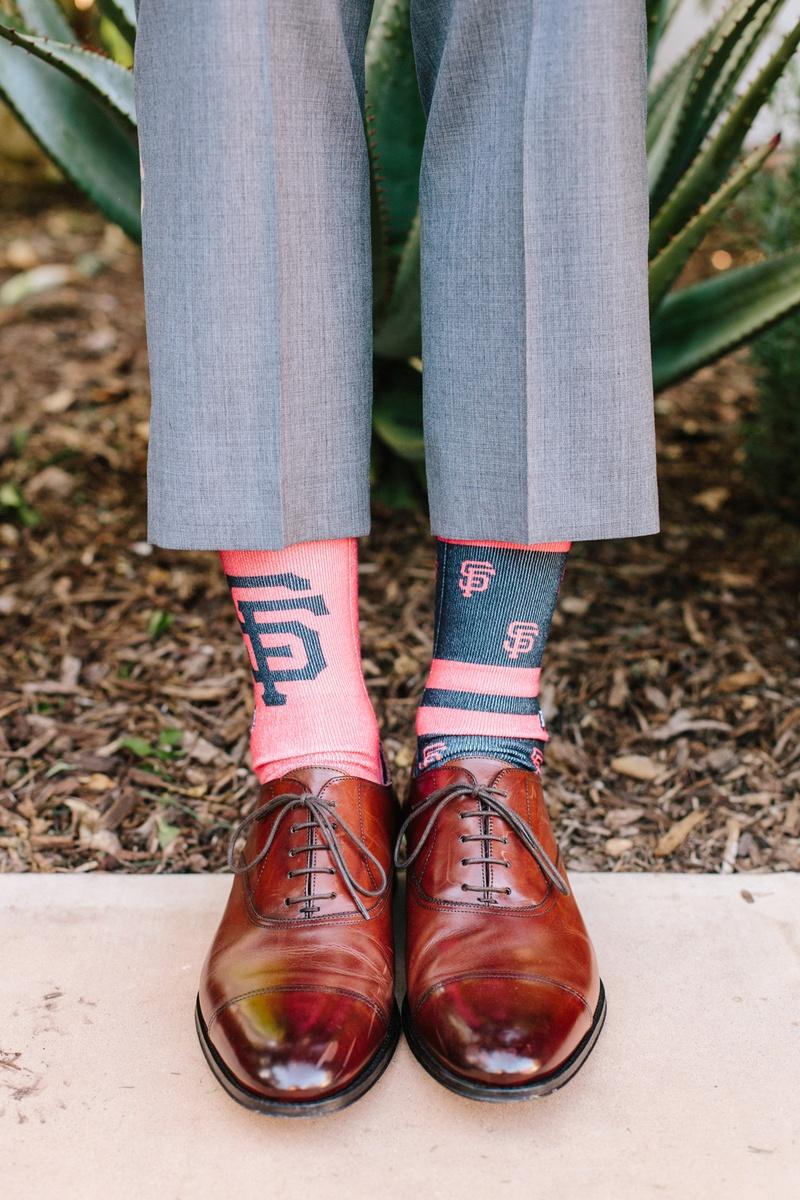 groom in grey suit, brown shoes, mismatched san francisco giants socks
