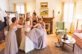 bridesmaids playfully help bride into her wedding dress while laughing