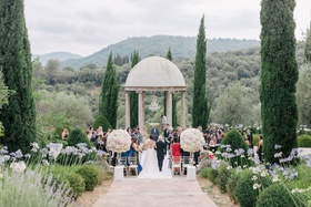 Wedding ceremony in South of France outdoors at chateau rotunda large flower arrangements aisle