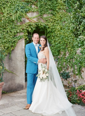 Bride in strapless gown and groom in blue suit and brown shoes bow tie italy wedding