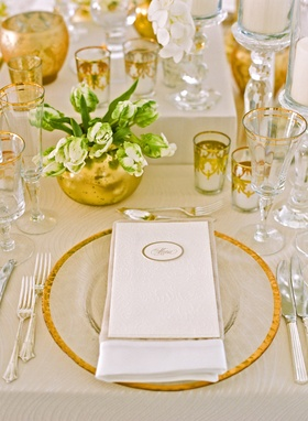 Gold candle votives, vases, glasses, and charger at wedding
