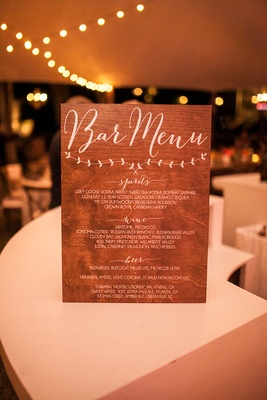 Wood sign with bar menu in calligraphy spirits wine beer selections at wedding reception