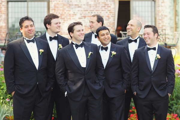 Groom with six friends with hands in tux pockets