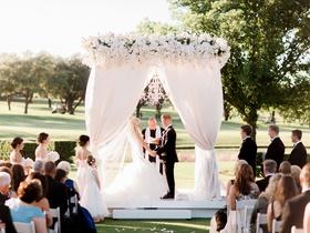 Bride in wedding dress black tux on groom chandelier outdoor wedding ceremony all white decor flower