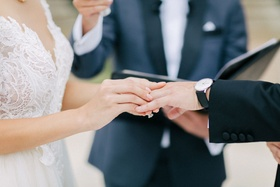 Bride sliding wedding ring on groom's finger during outdoor wedding ceremony illusion gown
