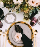 Wedding reception top view black napkin pink flower gold flatware hexagon marble name plate colors