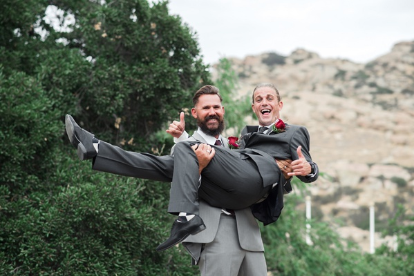 groomsman in light grey suit picks up and carries groom in charcoal grey suit