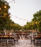 dark wood tables and chairs with trees, bistro lights, courtyard wedding reception, unique tile