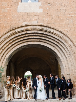 bride and groom kiss in umbria italy with bridesmaids gold champagne wedding dresses groomsmen suits