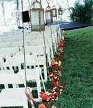 Outdoor ceremony with white chairs and lanterns