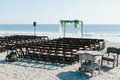 ceremony space beach wood chairs arch greenery sand wedding oceanside california