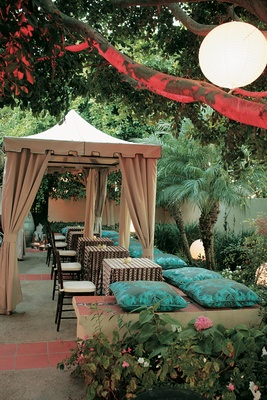 Outdoor cabana wedding reception with pillows on bench