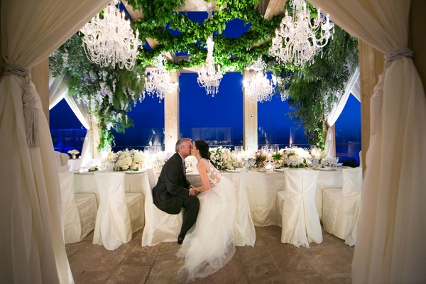 Bride and groom at head table vow renewal kiss as sun goes down chandeliers overhead candlelight