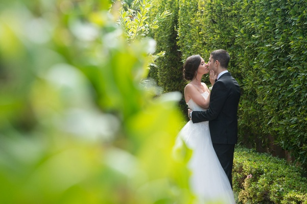 Hedge wall garden greenery bride in monique lhuillier wedding dress groom in tuxedo kiss strapless