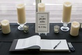 a guest book ceremony for well wishes on black tablescape with low candles