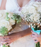 Bride's bouquet of white flowers and touches of green, bridesmaid bouquet of baby's breath, roses