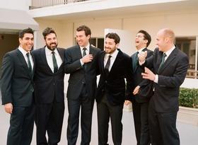 Men in dark suits with striped green ties