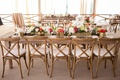 Gold box centerpieces holding white, pink, and orange flowers on top of rustic wood tables and chair