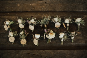 two row of boutonnieres made with sea holly and ivory blooms