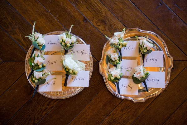 wedding boutonniere on silver tray with name tags white rose and berries greenery