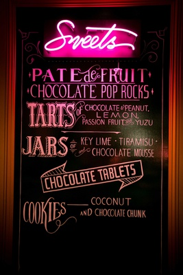chalkboard with neon sign displaying sweets at dessert bar