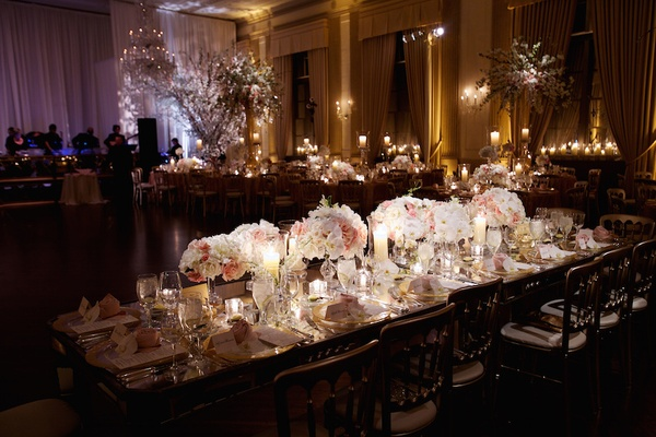 Mirrored wedding head table with arrangements of white and pink orchids, roses, and hydrangeas