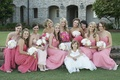 Bride with bridesmaids in long dresses in varying shades of pink