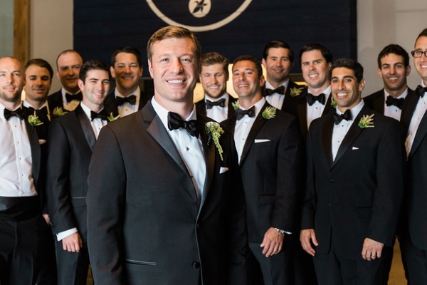 groom and groomsmen black and white tuxedoes smile