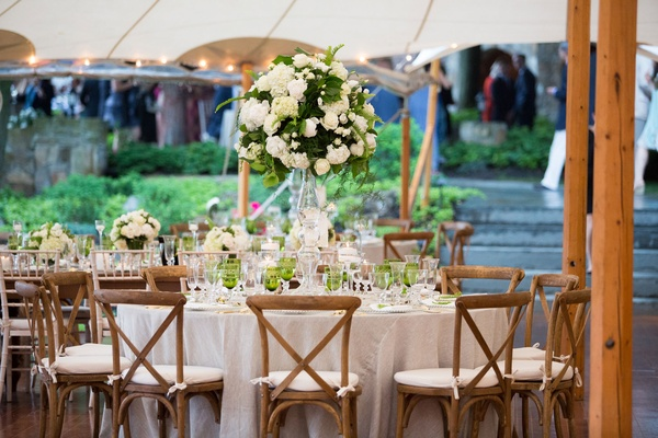 Rustic wedding under tent green glassware colored tall flower arrangement wood chairs white cushions