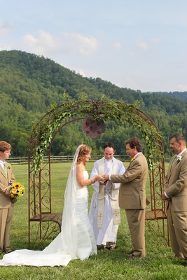 Bride and groom under wrought iron arch with leaves